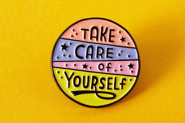 """Take care of yourself"" enamel pin on a yellow background"